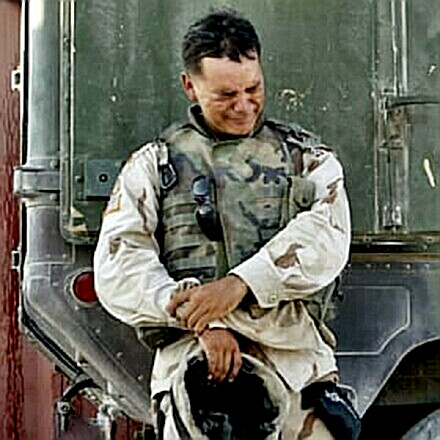A soldier weeps by his vehicle in Iraq